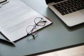 eyeglasses with black frame beside macbook pro